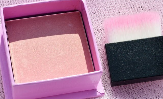 Image of the blusher open with the brush next to it showing the shade, and shimmer finish of the blush