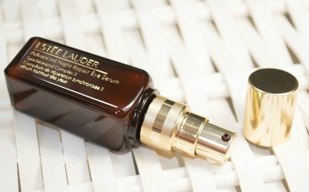 Eye serum tube packaging lying on its side with the pump and lid
