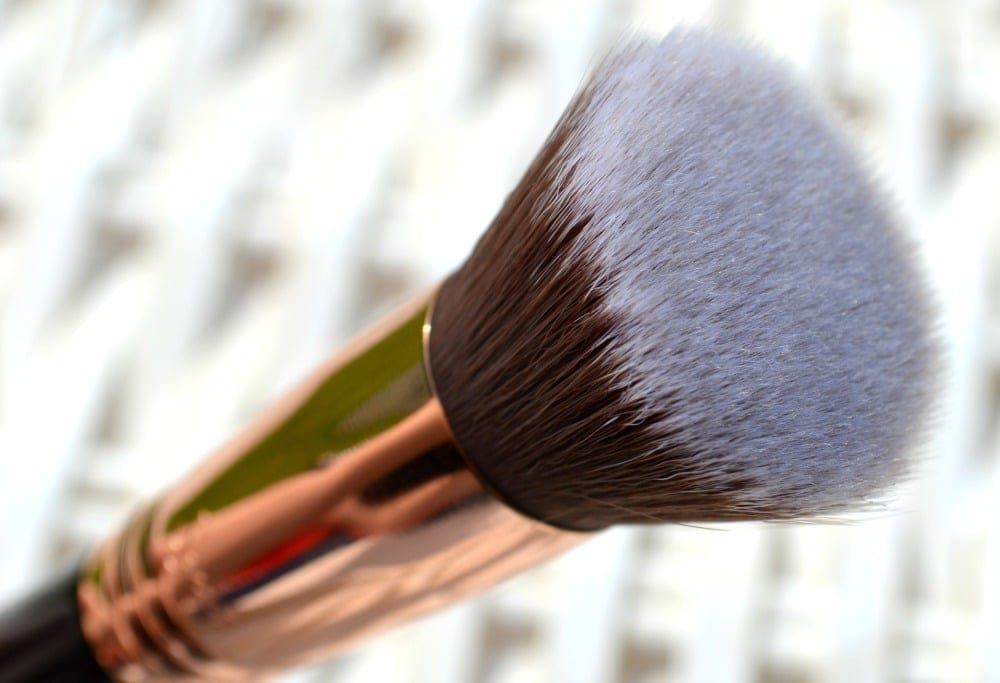 Close up image of the flat top bristles of the makeup brush with the rose gold ferrule