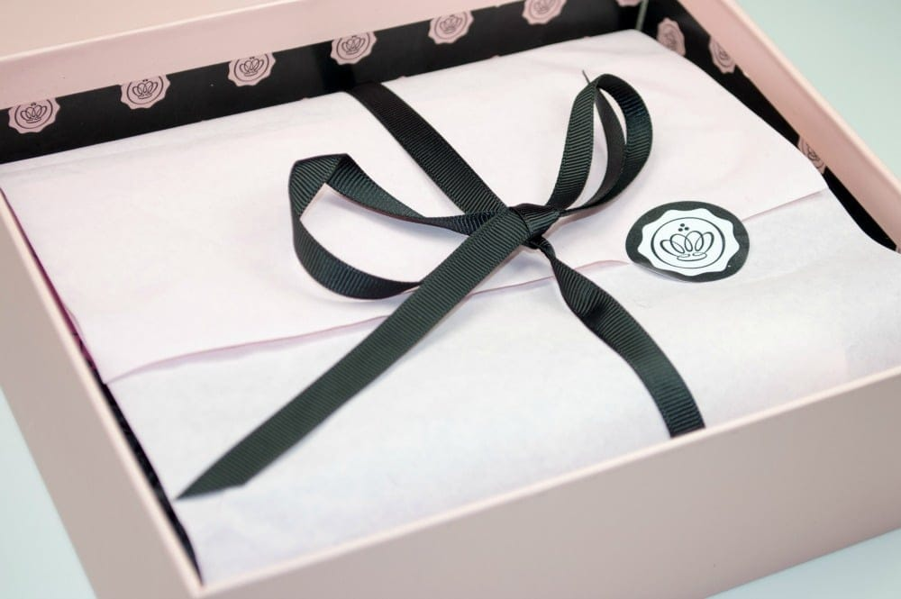 Image showing the inside of the box with pink tissue paper tied together with a black ribbon