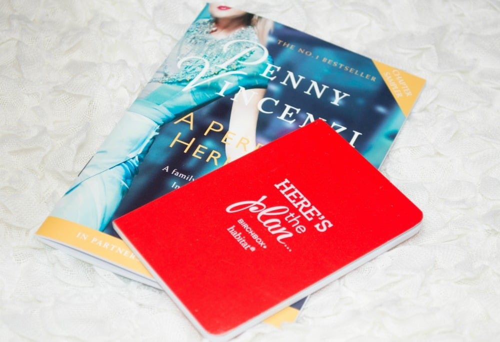 Image of a small red notebook and a sample chapter of a book