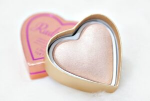 Review and Swatches of the I Heart Revolution Radiance Glow Hearts Highlighter - a triple baked highlighter in a glittery pale gold shade.
