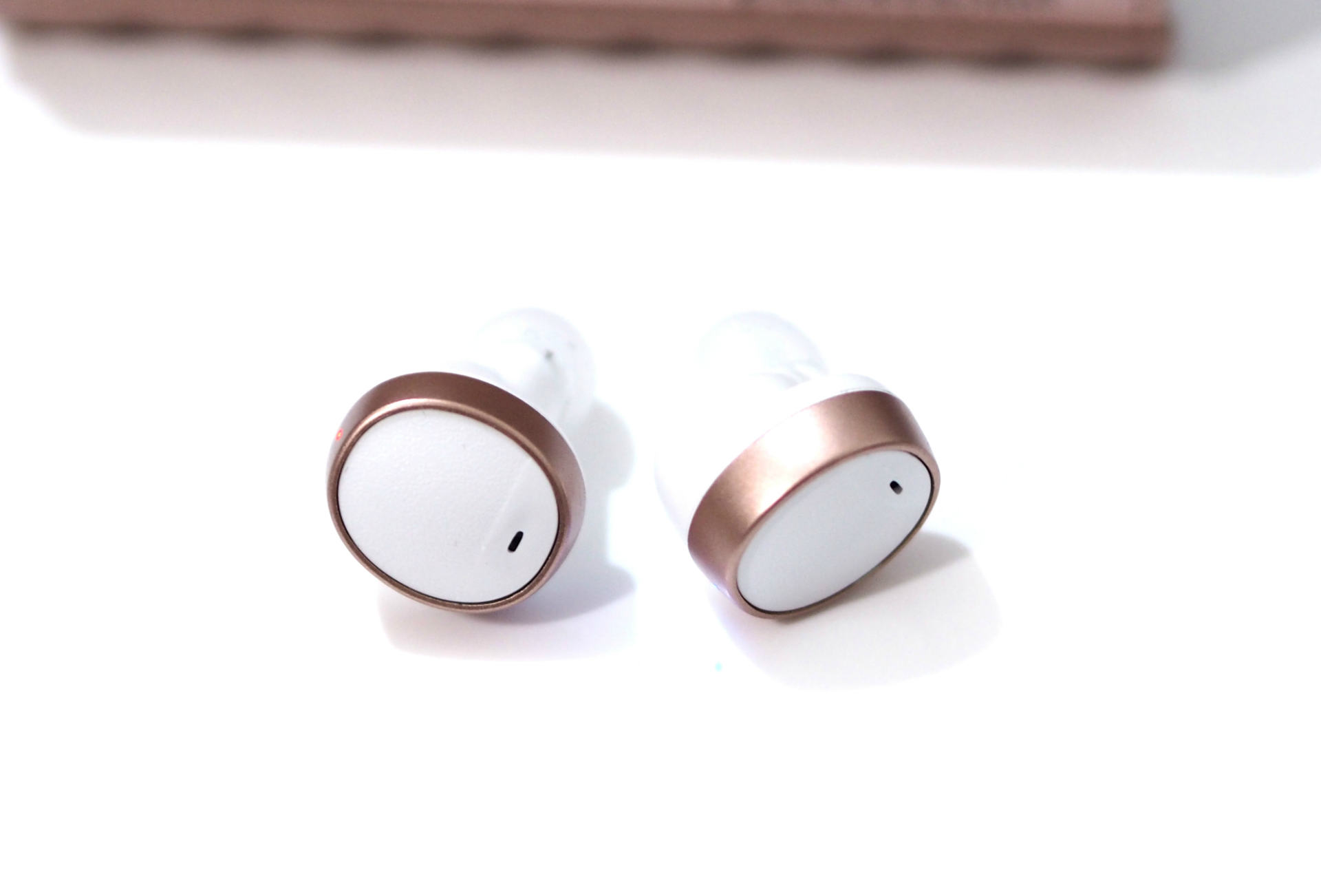 Close up of the white and rose gold earphones